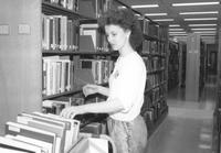 Library worker shelves books in Memorial Library at Mankato State University