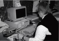 Library worker using a computer in the library at Mankato State University
