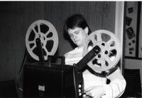 Student worker setting up a film onto a projection reel in the library at Mankato State University