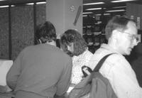 Library worker assists a patron in checking out a book in Memorial Library at Mankato State University
