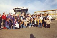 A large group of Mankato State University football fans pose for a picture before leaving on a bus to go to the conference championship football game, 1987.