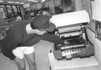 Library worker attempts to fix a copy machine in Memorial Library at Mankato State University