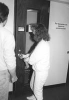 Library worker unlocking door to the typewriter carrel for a patron in Memorial Library at Mankato State University.