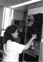 A worker using buttons to set up a reel to reel machine at Mankato State University