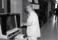 Student worker working on a microfilm machine in the library at Mankato State University