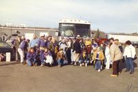 A large group of Mankato State University football fans get ready to pose for a picture before leaving on a bus to go to the conference championship football game, 1987.