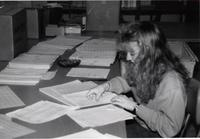Student worker going through papers at work in the library at Mankato State University