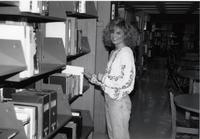 A student worker shelving items in the library at Mankato State University