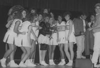 A picture of the 1988 Mankato State University Homecoming queen, cheerleaders and Stomper (back L) in the Centennial Student Union Ballroom.