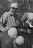 Mankato State University, a man speaks during Homecoming with the Maverick mascot in the background, 1988