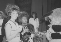 "A picture of the 1988 Mankato State University Homecoming queen enjoying refreshments with a cheerleader and the MSU mascot ""Stomper."""