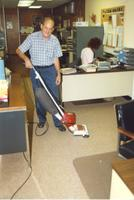 A man shown vacuuming in an office, Mankato State University, 1987.