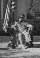 Mankato State University, the Homecoming King sits in a chair on the Campus Mall during Homecoming, 1988