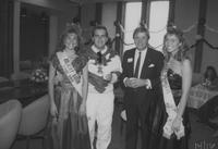 A picture of Connie David as the Kolacky Queen and Chrissy Dietz as the Kolacky Princess and two other men participating during a 1988 Mankato State University Homecoming event.