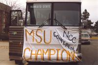 A charter bus with a banner celebrating Mankato State University's title as NCC Conference Champions in football.