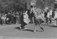 Mankato State University, the Homecoming King and Maverick mascot dance on the Campus Mall during Homecoming, 1988