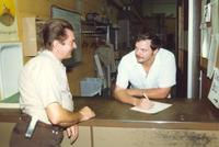 Two men talking at a counter, Mankato State University, 1987.