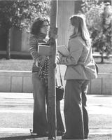 Two females standing and talking outside of Armstrong Hall on the Campus Mall, Mankato State University in the late 1970's.
