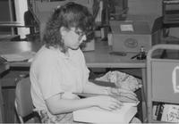 Mankato State University library student worker fixing a book. Picture was taken in the late 1980's.