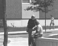 Two male students talk to each other outside of Mankato State College's Nelson Hall, 1970s.