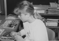 Mankato State University library student worker putting sticker on periodicals. Picture was taken in the late 1980's.