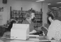 Mankato State University female library staff member helping a female check out equipment. Picture was taken in the late 1980's.