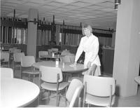 A female worker cleaning a table in the dining area of the centennial student union at Mankato State College 1968-03-07