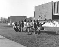 A group of 12 cheerleaders practice a cheer in front of the Mankato State University Centennial Student Union, 1970s.