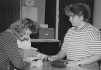 Mankato State University female library staff member helping a female check out equipment. Picture taken in the 1980s.