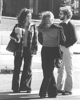 Two females and a male standing and talking outside of Armstrong Hall on the Campus Mall. Mankato State University in the late 1970's.