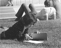 Female laying in the grass on the Campus Mall doing homework. Mankato State University in the late 1970's.