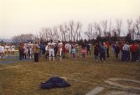 Football players, cheerleaders, and fans standing on the football field talking after the Mankato State University victory over South Dakota State University. November 14, 1987.