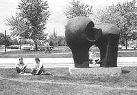 Two Mankato State College male students sit in the grass by the Chthonic Sculpture looking at a book, another two students are visible in the background, 1970.