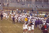 Mankato State University football team, coaches, and cheerleaders walking out on the field after their victory over South Dakota State University at Blakeslee Stadium. November 14, 1987.