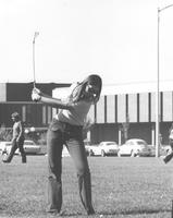 A woman practices her golf swing in front of Morris Hall and the Centennial Student Union, 1970s.