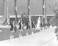 Eight Mankato State University women stand and hold flags in front of the Memorial Library, 1970s.