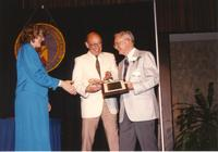 Two males receiving an award by Margaret Preska at the retirement banquet located in the Centennial Student Union. Mankato State University, June 1, 1989.