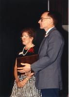 A male and a female standing on stage with an award at the retirement banquet located in the Centennial Student Union. Mankato State University, June 1, 1989.