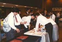 A group of individuals standing around tables and giving out information in the Centennial Student Union Ballroom for Career Week, Mankato State University