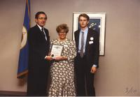 One woman receiving an award from Former Minnesota governor Rudy Perpich (L), with unknown man on the right, Mankato State University