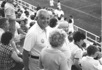 Bob Otto standing in bleachers smiling for the photograph at MSU football game; Unidentified men and women surrounding Bob Otto; Mankato State University; 1985