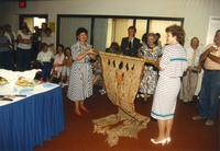 Two women presenting a gift at Donna Evans Retirement. Mankato State University, August 3, 1989.