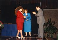 Female walking on stage to receive an award from Margaret Preska at the retirement banquet located in the Centennial Student Union. Mankato State University, June 1, 1989.