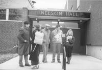 A group of unidentified students stand and socialize in front of Nelson Hall, Mankato State University, Mankato