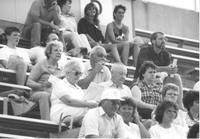 Bob Otto in middle of crowd watching football game; Seven unidentified males sitting in the bleachers with eleven unidentified women looking away from camera; Mankato State University; 1989