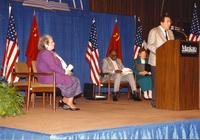 A group of unidentified individuals sitting on stage and a man giving a speech in the Centennial Student Union Ballroom, Mankato State University