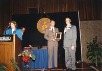 Winston Benson receiving an award with Margaret Preska announcing it at the Retirement Banquet located in the Centennial Student Union June 1, 1989.