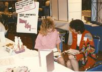 Two unknown women, a student (L) and a faculty (R), sits down in the Centennial Student Union Ballroom for Career Week and informs and asks one another for information, Mankato State University