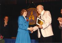 Male shaking hands with Margaret Preska at the retirement banquet located in the Centennial Student Union. Mankato State University, June 1, 1989.