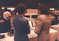 Two unidentified women talk about the Wausau Insurance Companies in the Centennial Student Ballroom, Mankato State University